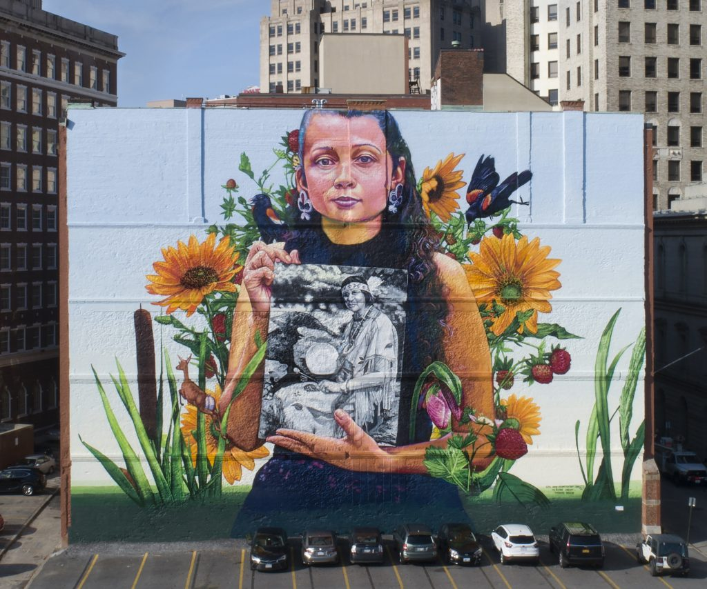 Still Here, in Providence, depicts Narragansett artist Lynsea Montanari holding a portrait of Narragansett/Wampanoag leader Princess Redwing.