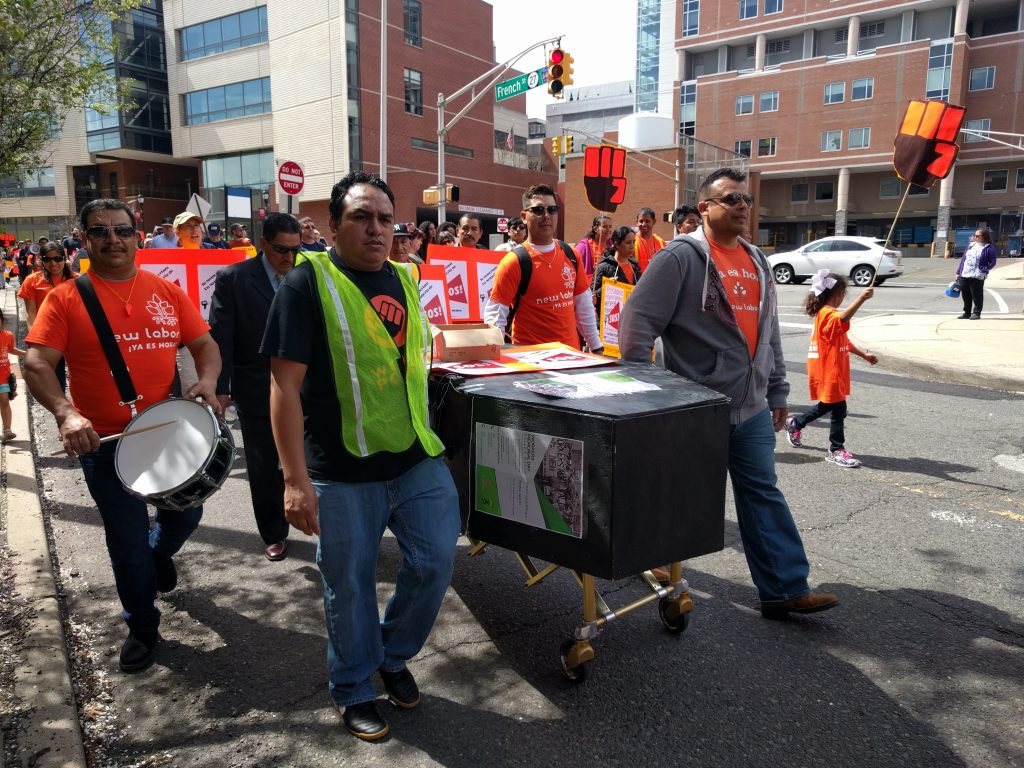 "2017: Workers march through New Brunswick with faux coffin, chanting ""ni una muerte más."""