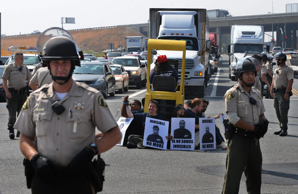 Warehouse workers block truck traffic, choking the supply chain to advocate for labor rights, 2009.